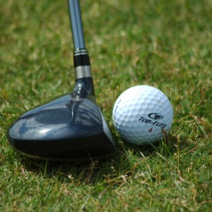Golf_ball_resting_near_fairway_wood